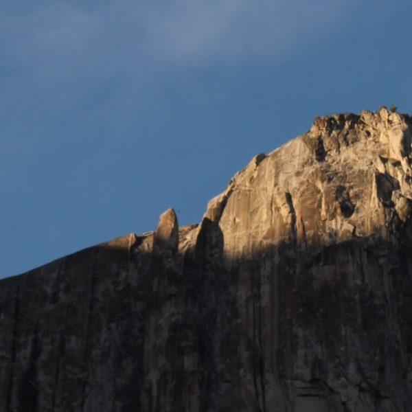 """Zoom donde se ve un pequeño punto (el escalador) en el aire entre la roca """"suelta"""" y la cima"""