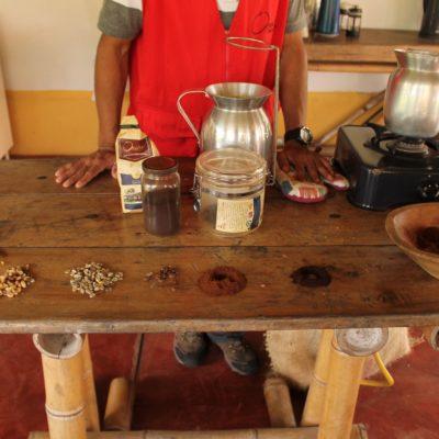 En fila en la mesa, de izq. a der.: grano de buena calidad, grano de mala calidad, pergamino, grano tostado, grano de primera calidad molido y el de segunda calidad molido. ¿De cual de los dos colores es el café molido que tomáis?