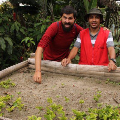 Nico con el guía del tour frente a la primera fase de la plantación del café