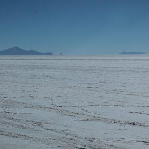 Por la luz del sol reflejada en la sal, parece que los bordes de las montañas se vuelvan hacia dentro, como si las montañas flotaran