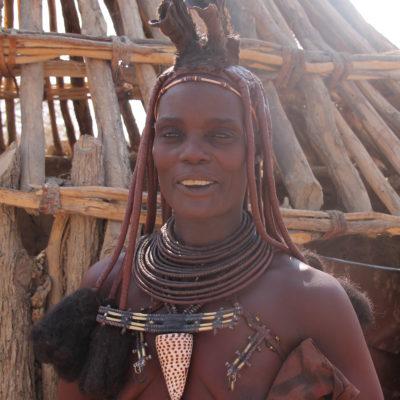 """Una mujer himba casada, además de las rastas, lleva un tocado de piel en la cabeza y muchas """"joyas"""" alrededor del cuello y pecho"""