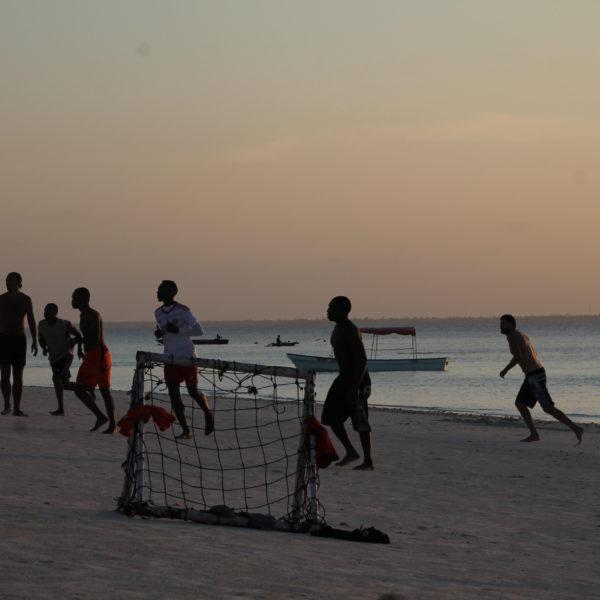 Nico jugando con los locales en la playa al atardecer