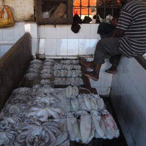 """Un puesto de pulpos, calamares y pescado del mercado y sus """"pescateros"""""""