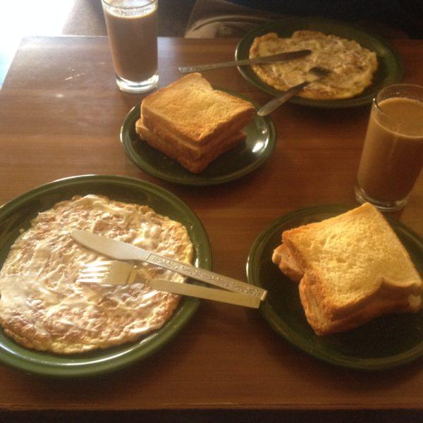 Gran desayuno a base de tortilla con queso, tostadas y té masala