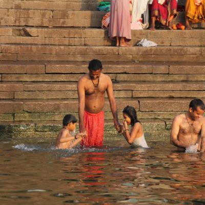 Un padre sujeta a sus niños mientras éstos se sumergen en las aguas del Ganges