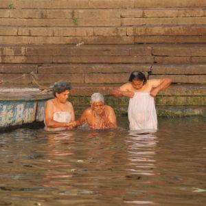 Hombres y mujeres se sumergen por completo en el río