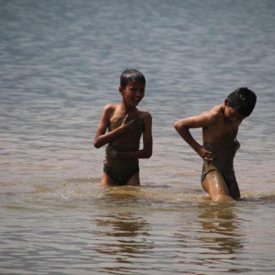 Niños jugando con el barro del fondo del lago
