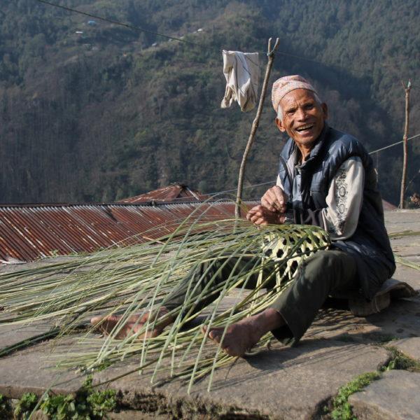 Un hombre nepalí feliz haciendo su cesta