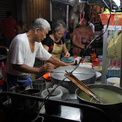 Una pareja mayor cocinando los noodles de toda la vida