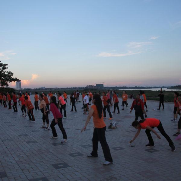 Varios grupos de gente hacían gimnasia en forma de aerobic en el paseo junto al río